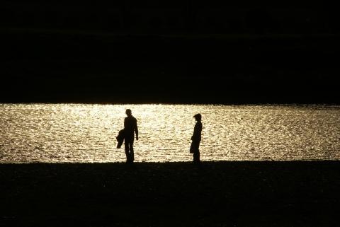 夕日の川原を歩く初老の御夫婦