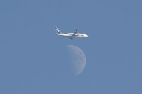 月の上側を飛ぶ全日空機